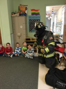 Fire fighter talking to children